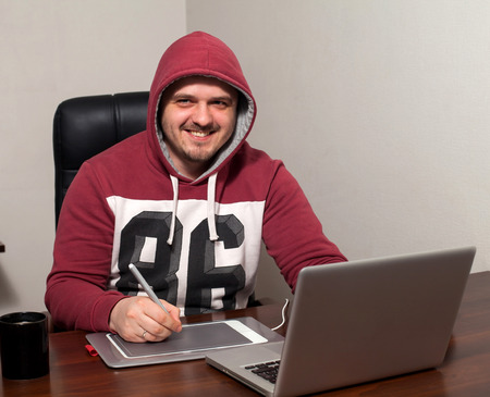 smiing: Attractive man is going to do retouching work on laptop