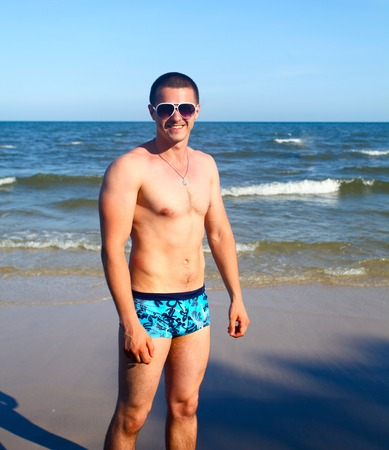 swimming trunks: A handsome young man in swimming trunks and sunglasses standing in the sand with ocean in background