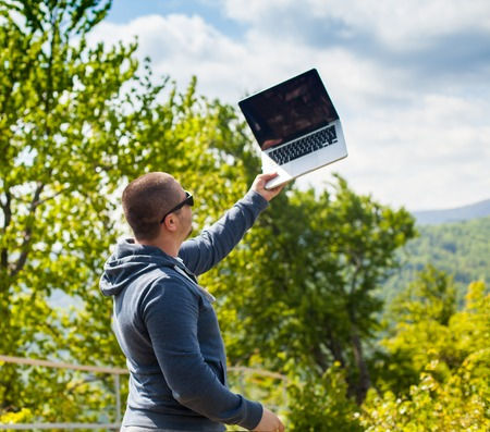 conection: The man in glasses is trying to catch a connection with his laptop on the background of nature.