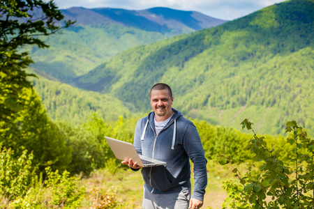 conection: Smiling man is trying to catch a connection with his laptop on the background of mountains.