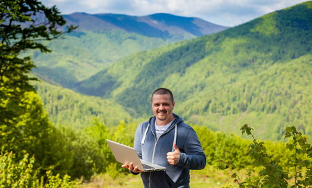 conection: Smiling man cought a connection with his laptop on the background of mountains.
