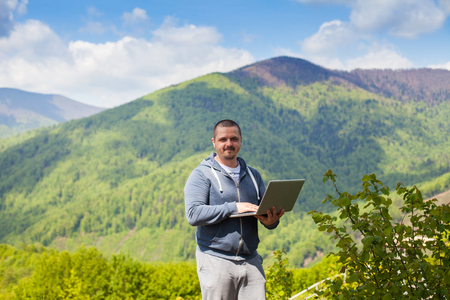conection: The man is trying to catch a connection with his laptop on the background of mountains with beautiful blue sky. Stock Photo