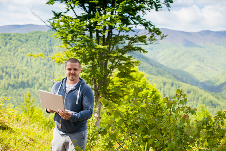 conection: The man in grey sport pants is trying to catch a connection with his laptop on the background of green mountains.