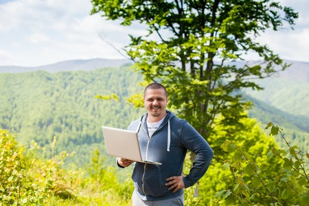 conection: The man in grey pants is trying to catch a connection with his laptop on the background of green mountains.