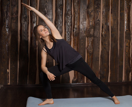 side angle pose: Young and beauty woman is doing side angle pose exercise in yoga classes with wooden background. Stock Photo
