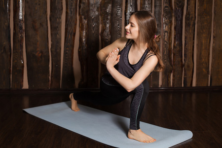 side angle pose: Strong and young woman is in Reverse Side Angle pose  in yoga classes with wooden background. Stock Photo