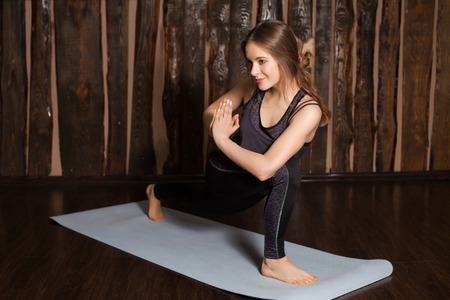 side angle pose: Strong and beauty woman is in Reverse Side Angle pose  in yoga classes with wooden background. Stock Photo