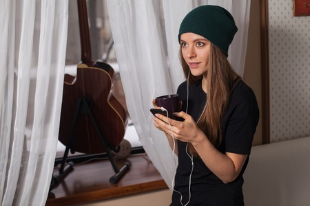 enjoying life: Woman hipster in green hat listening music and enjoying life