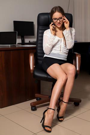 sexy secretary: Secretaria atractiva está discutiendo trabajo de negocios en el teléfono que se sienta en la silla Foto de archivo