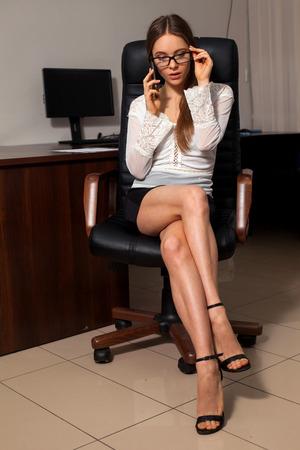 sexy secretary: secretaria atractiva vestida bien está sentado en la silla durante la conversación telefónica de negocios