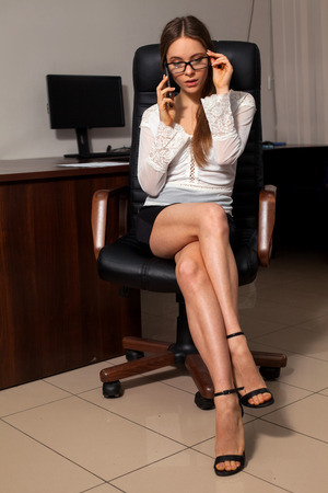 welldressed: Well-dressed sexy secretary is sitting on the chair during business phone conversation
