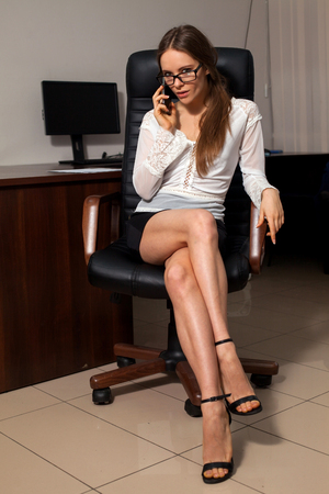 sexy secretary: Well-dressed sexy secretary is sitting on the chair during business phone conversation