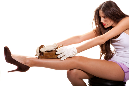 young  woman sharpens her legs with wooden jack-plane