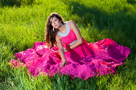 Young woman in an airy dress sitting on green grass Stock Photo