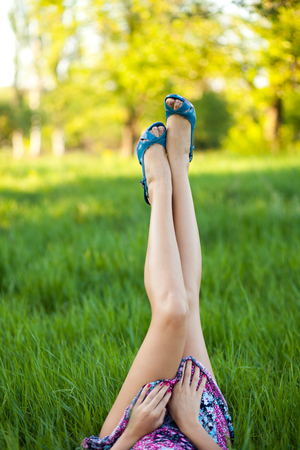 Bared legs in the shoes of young woman, which is lying on green grass