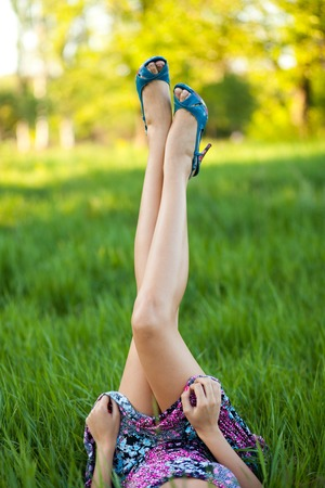 bared: Bared legs in the shoes of woman, which is lying on green grass Stock Photo