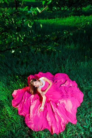 Cute young woman in an airy dress sitting on green grass Stock Photo