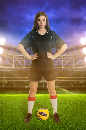 sports field: Woman soccer player with soccer ball at stadium Stock Photo