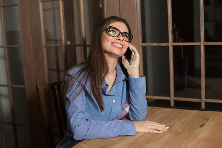 smilling: Woman is listening someone on the phone and smilling