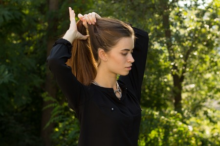 Attractive young  woman in black blouse with silver necklace fixing her long brown hair on the background of green trees