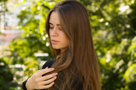 silver hair: Young beautiful woman with brown long hair in black blouse and silver necklace on the background of green trees