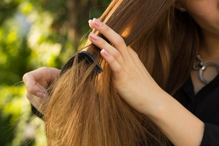 Young woman in black blouse and silver necklace combing her straight  long hair on the background of green trees Stock Photo