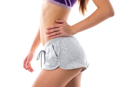 Young woman in purple sports top and grey shorts showing her buttocks and abdominals on white background in studio