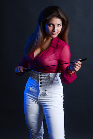 Portrait of young girl of the uniformed horseman which holds a whip in hands and looks a tempting look