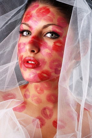 kissing mouth: woman with stamps of lipstick on her face and veil