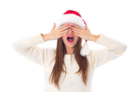 Pretty young woman in white sweater with red christmas hat closing eyes on white background in studio Stock Photo
