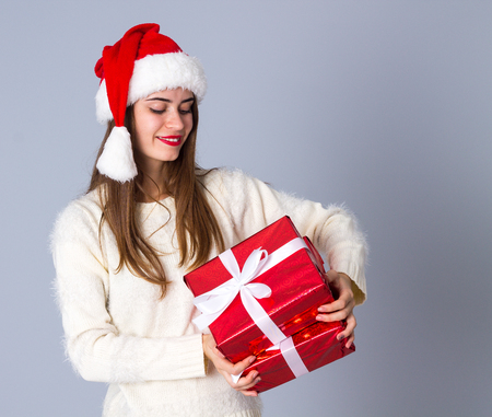 them: Young charming woman in white sweater with long hair and red christmas hat holding presents and looking at them on grey background in studio