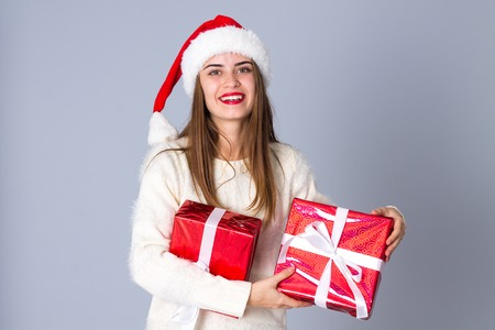 Young happy woman in white sweater with long hair and red christmas hat holding presents on grey background in studio