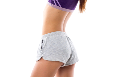 abdominals: Young athletic woman in purple sports top and grey shorts showing her buttocks and abdominals on white background in studio