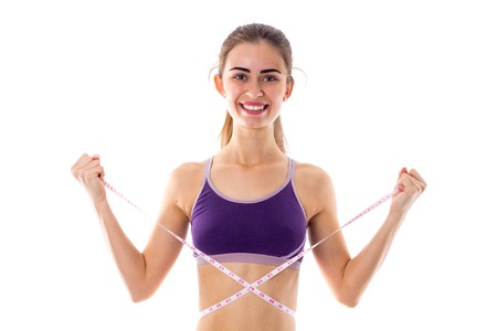 ponytail: Smiling young woman in purple sports top with ponytail using centimeter on white background in studio
