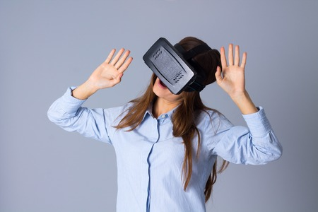 Young pretty woman in blue shirt using VR glasses on grey background in studio