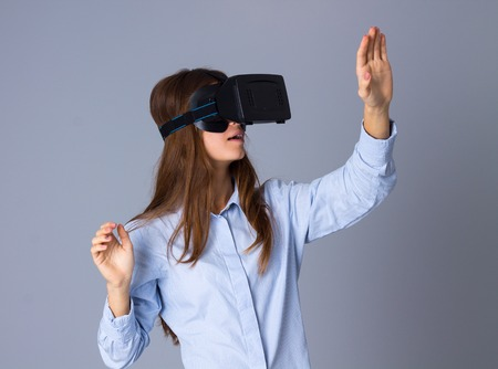 Young beautiful woman in blue shirt using VR glasses and touching something on grey background in studio
