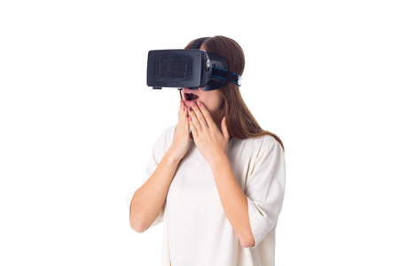 Young beautiful woman in white shirt using virtual reality glasses on white background in studio