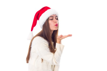 Young charming woman in white sweater with red christmas hat sending air kiss on white background in studio Stock Photo