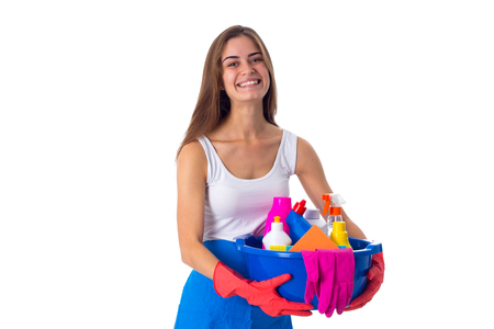 Young smiling woman in white shirt and blue apron with red gloves holding cleaning things in blue washbowl on white background in studio