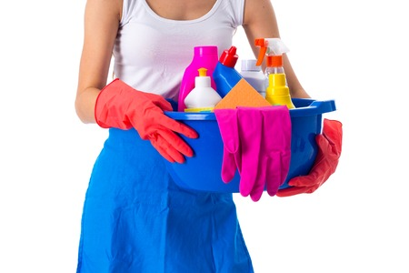 Woman in white shirt and blue apron with red gloves holding cleaning things in blue washbowl on white background in studio