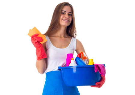 Young positive woman in white shirt and blue apron with red gloves holding cleaning things in blue washbowl on white background in studio
