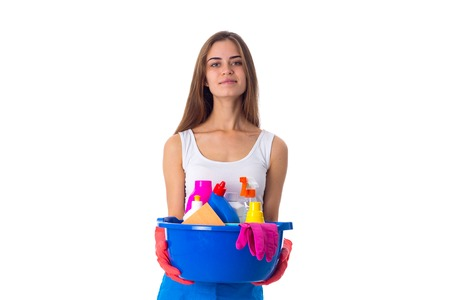 Young beautiful woman in white shirt and blue apron with red gloves holding cleaning things in blue washbowl on white background in studio Stock Photo