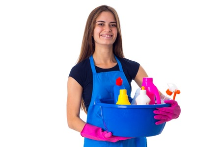 washbowl: Young smiling woman in blue T-shirt and apron with pink gloves holding cleaning things in blue washbowl on white background in studio Stock Photo