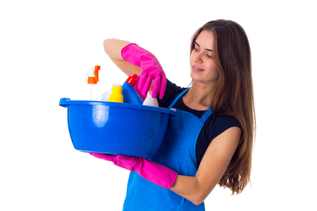 washbowl: Young attractive woman in blue T-shirt and apron with pink gloves holding cleaning things in blue washbowl on white background in studio