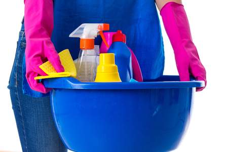 washbowl: Young woman in jeans and apron with pink gloves holding cleaning things in blue washbowl on white background in studio