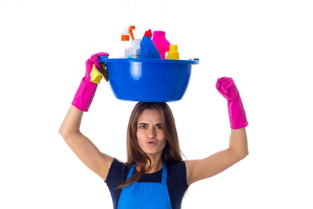 washbowl: Young pretty woman in blue T-shirt and apron with pink gloves holding cleaning things in blue washbowl on her head on white background in studio. Stock Photo
