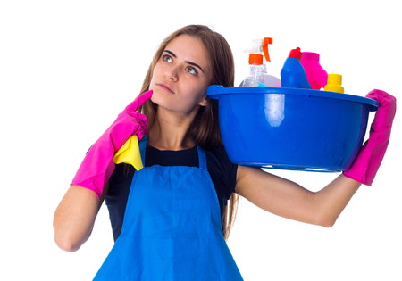 Young pretty woman in blue T-shirt and apron with pink gloves holding cleaning things in blue washbowl and thinking on white background in studio