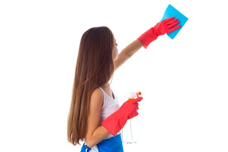 Young woman in white shirt and blue apron with gloves using duster and detergent on white background in studio Stock Photo
