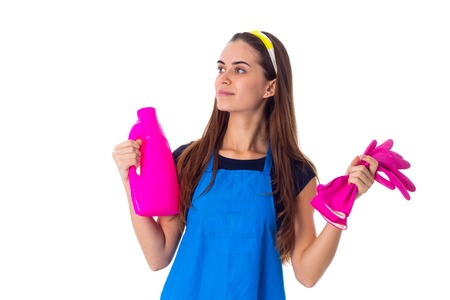 Nice young woman in blue T-shirt and apron holding pink gloves and detergent on white background in studio