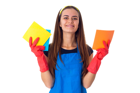 Young nice woman in blue T-shirt and apron with red gloves holding dusters on white background in studio Stock Photo